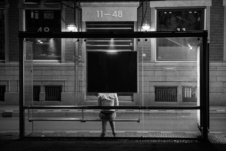image from behind of a person waiting at a bus stop