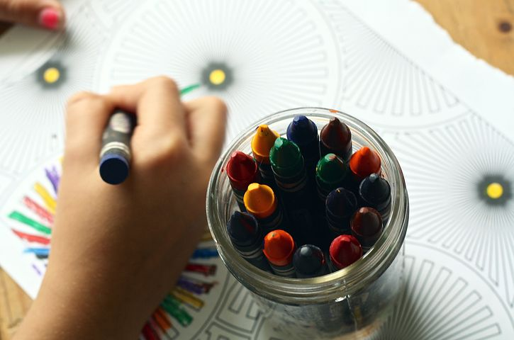 A child's hand drawing with crayons