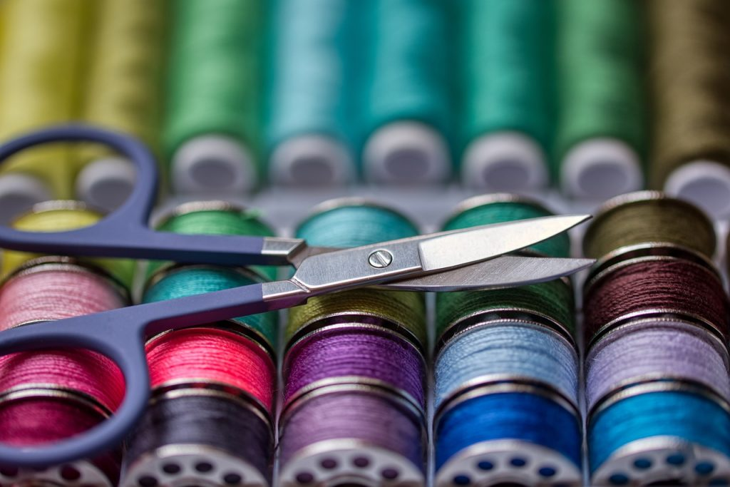 spools of colored thread with scissors on top
